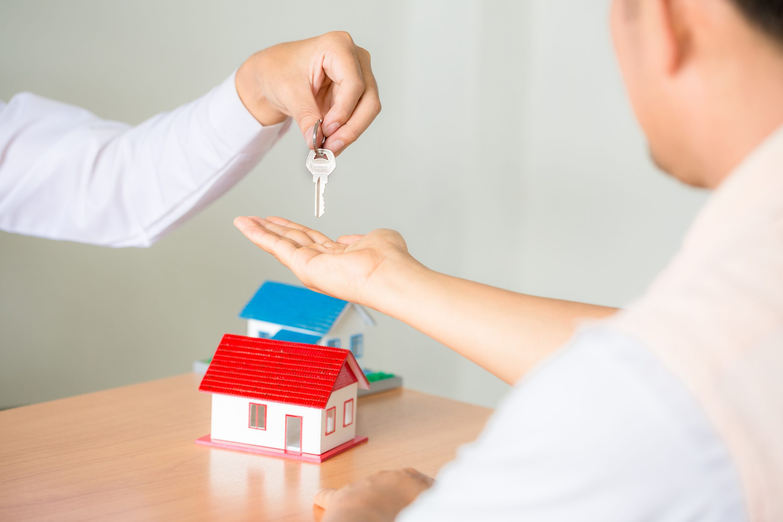 Real estate Sales manager giving keys to customer after signing rental lease contract of sale purchase agreement, concerning mortgage loan offer for and house insurance.